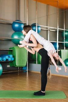 Mujer joven con su pequeña hija linda en la espalda durante el ejercicio