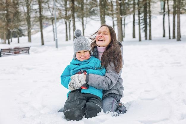 Mujer joven con su pequeño hijo jugando en la nieve en invierno