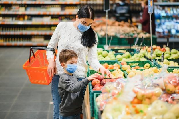 Mujer joven y su pequeño hijo con máscara protectora comprar comida en un supermercado