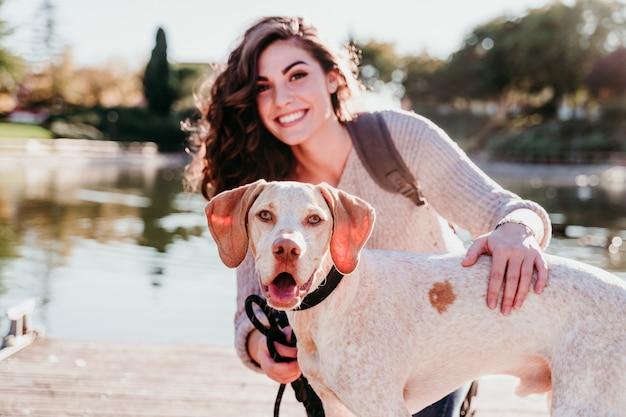 Mujer joven y su perro al aire libre en un parque con un lago. día soleado, temporada de otoño