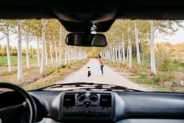Mujer joven y su perro border collie caminando por un camino de árboles. vista desde el interior de la camioneta. concepto de viaje y mascotas