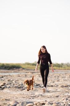 Mujer joven con su perro caminando