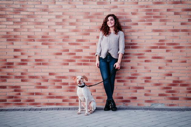 Mujer joven y su perro en la ciudad. de pie junto a una pared de ladrillos
