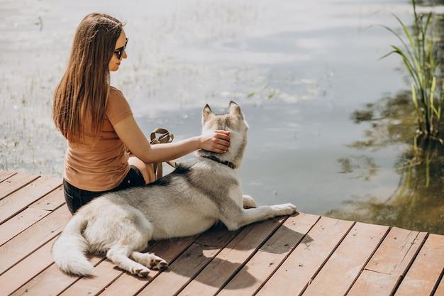 Mujer joven con su perro husky junto al lago