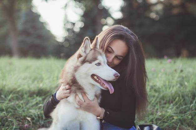 Mujer joven y su perro husky
