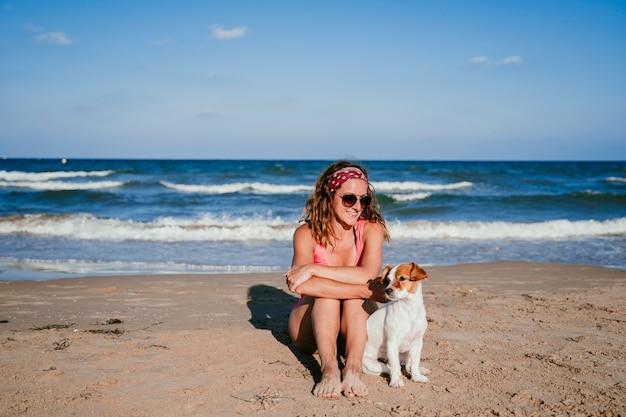 Mujer joven y su perro sentado en la playa.