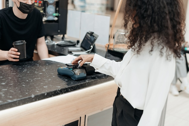 Mujer joven con su teléfono inteligente para pagar en el supermercado