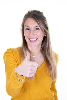 Mujer joven en sudadera amarilla mostrando signo bien dando un pulgar arriba gesto