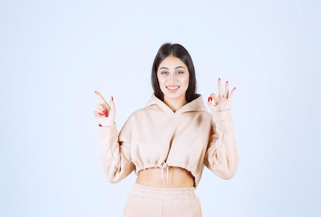 Mujer joven en una sudadera con capucha rosa mostrando buen signo de mano