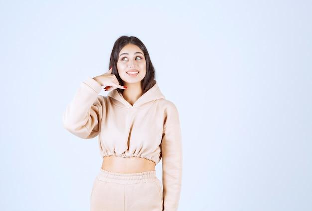 Mujer joven en una sudadera con capucha rosa pidiendo llamar