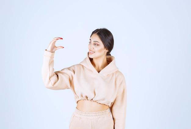 Mujer joven con una sudadera con capucha rosa que muestra la cantidad o el tamaño de un objeto