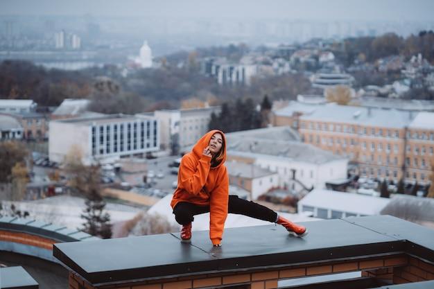 Mujer joven en una sudadera naranja plantea en el techo de un edificio en el centro de la ciudad.