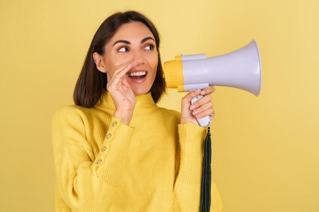Mujer joven en suéter amarillo cálido con altavoz de megáfono diciendo un secreto
