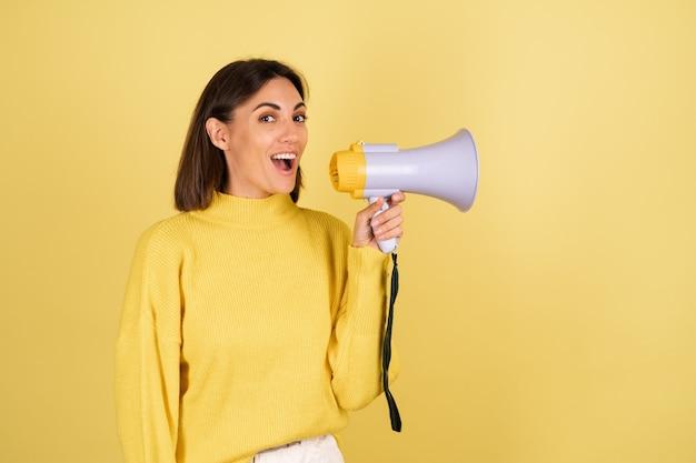 Mujer joven en suéter amarillo cálido con altavoz de megáfono emocionado y gritando