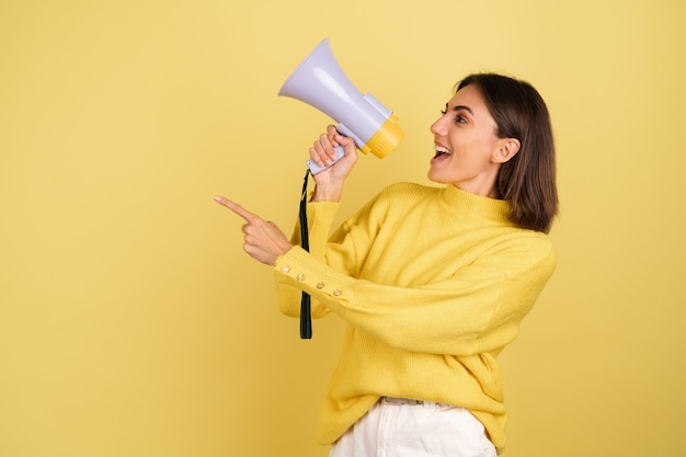 Mujer joven en suéter amarillo cálido con altavoz de megáfono gritando hacia el dedo índice apuntando hacia la izquierda