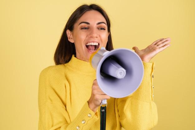 Mujer joven en suéter amarillo cálido con altavoz megáfono gritando