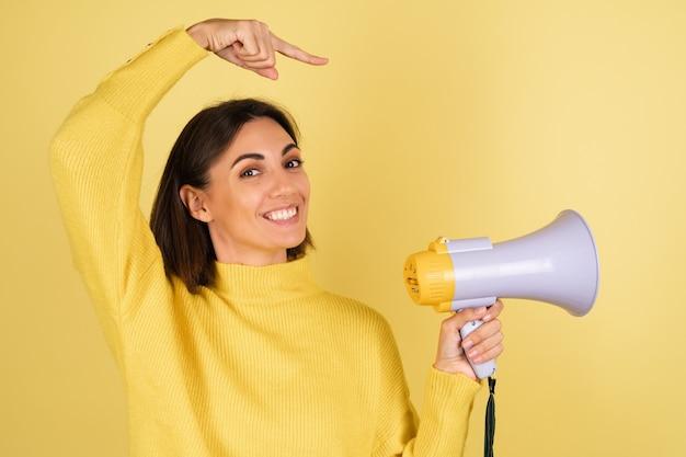 Mujer joven en suéter amarillo cálido con altavoz de megáfono y señalar con el dedo a la derecha
