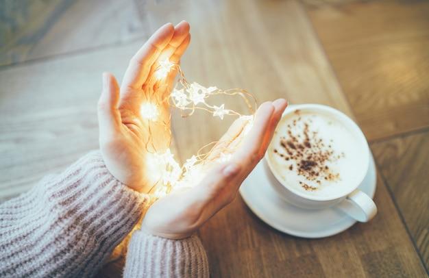 Mujer joven en suéter beige acogedor con corazón de guirnalda de estrellas