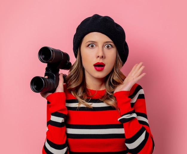 Mujer joven en suéter con binoculares en pared rosa