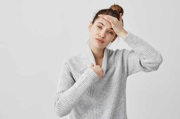 Mujer joven con suéter cálido de lana caliente tocando su cabeza tratando de desnudarse. especialista en seo femenino que siente falta de aire fresco expresando insatisfacción. concepto de sensación