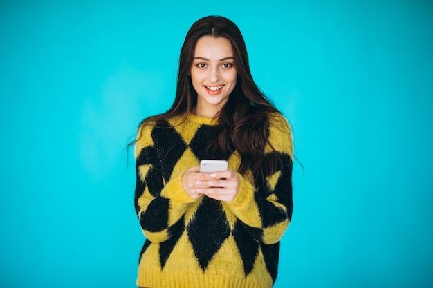 Mujer joven en un suéter caliente con teléfono