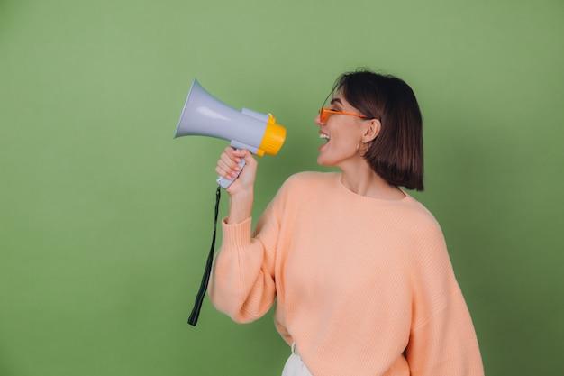 Mujer joven en suéter casual de anteojos de melocotón y naranja aislado en la pared verde oliva feliz gritando en el espacio de copia de megáfono