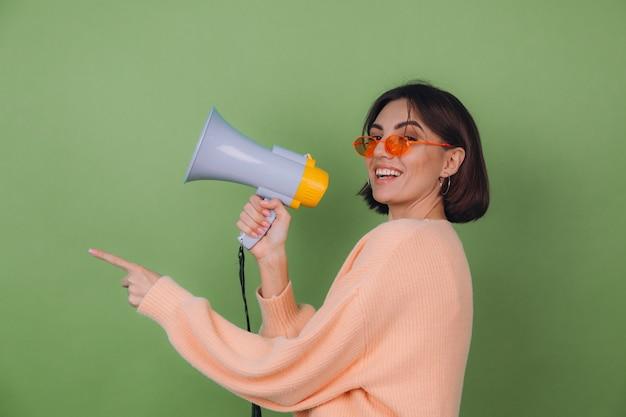 Mujer joven en suéter casual de anteojos naranja y melocotón aislado en la pared verde oliva feliz gritando en megáfono y apunta a la izquierda con el espacio de la copia del dedo índice