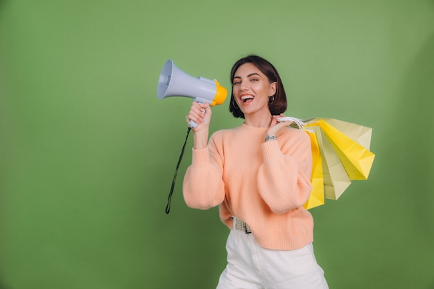 Mujer joven en suéter de melocotón casual aislado en la pared de color verde oliva grita en megáfono sosteniendo bolsas de compras, anuncia promoción de venta de descuentos