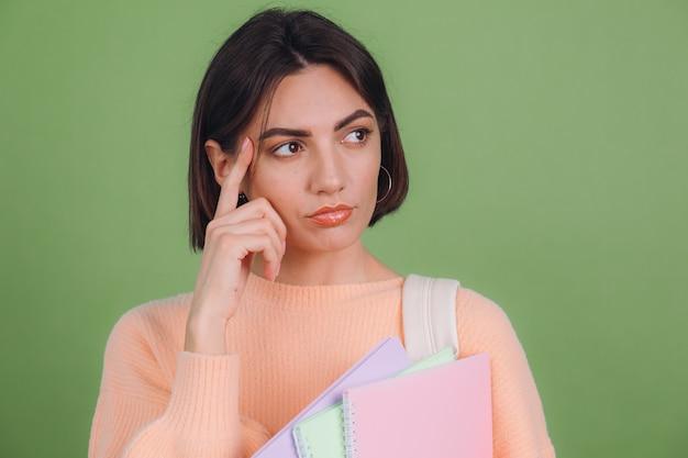 Mujer joven en suéter de melocotón casual aislado en la pared de color verde oliva