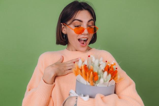 Mujer joven en suéter de melocotón casual aislado en la pared de olivo verde sostenga la composición de la caja de flor blanca naranja de flores de algodón, gypsophila, trigo y lagurus para un regalo feliz sorprendido