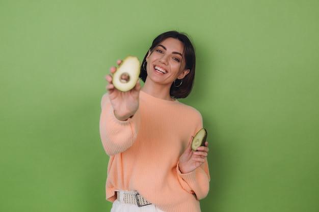 Mujer joven en suéter de melocotón casual aislado en la pared verde oliva con aguacate, concepto de salud y cuidado de la piel, espacio de copia