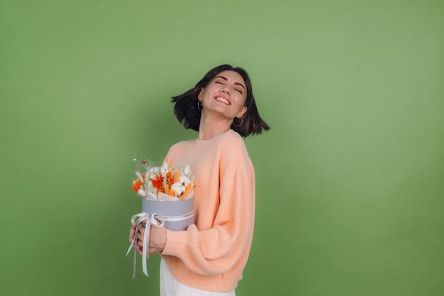 Mujer joven en suéter de melocotón casual aislado en la pared verde oliva sostenga la composición de la caja de flor blanca naranja de flores de algodón, trigo de gypsophila y lagurus para un regalo feliz sorprendido