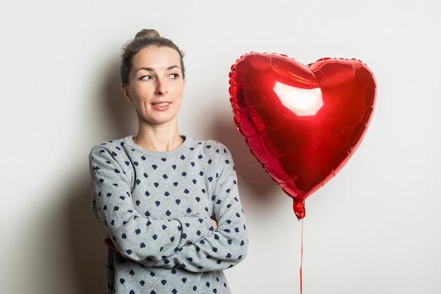 Mujer joven con un suéter mira el globo de aire de corazón sobre un fondo claro. concepto de día de san valentín.
