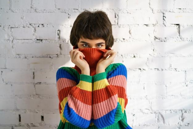 Una mujer joven con un suéter multicolor de brillantes colores se esconde el rostro y se tapa los oídos con las manos.