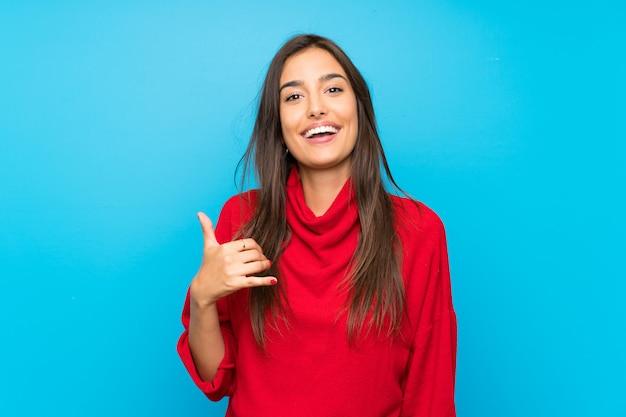 Mujer joven con suéter rojo aislado azul haciendo gesto de teléfono