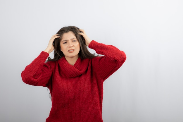Mujer joven en suéter rojo caliente que sufre de dolor de cabeza.