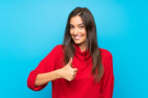 Mujer joven con suéter rojo dando un pulgar arriba gesto