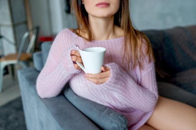 Una mujer joven en un suéter rosa mantiene la taza de café, primer plano