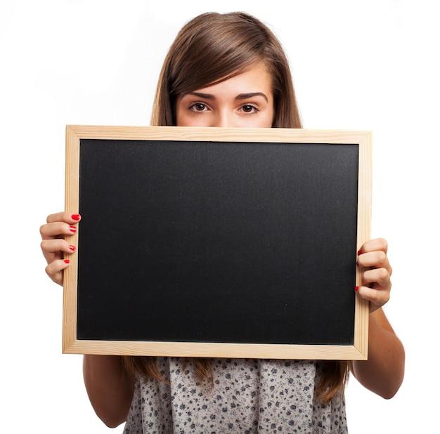 Mujer joven sujetando una pizarra debajo de sus ojos