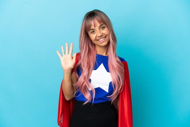 Mujer joven superhéroe con cabello rosado aislado sobre fondo azul contando cinco con los dedos