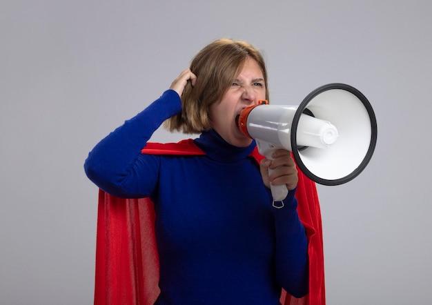 Mujer joven superhéroe rubia en capa roja mirando recto tocando el pelo gritando en altavoz aislado en la pared blanca