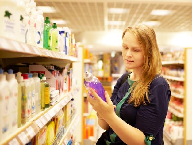 Mujer joven en el supermercado leyendo la inscripción