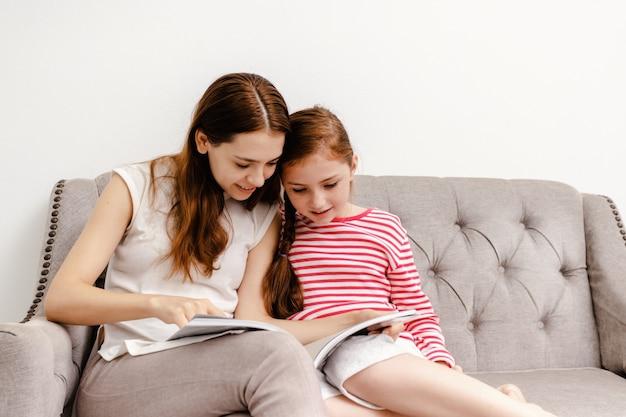 Mujer joven y sus libros de lectura de la hija de la niña que se sientan en el sofá en casa