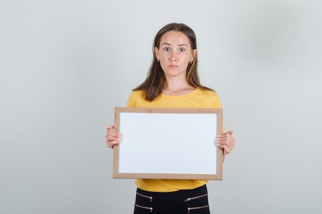 Mujer joven con tablero blanco en camiseta amarilla, pantalón negro y mirando con cuidado.