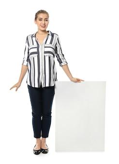 Mujer joven con tablero publicitario en blanco sobre fondo blanco.
