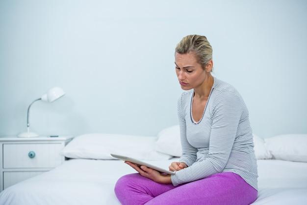 Mujer joven con tableta digital en cama