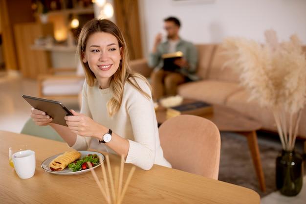 Mujer joven con tableta digital y desayunando en la cocina con un novio sentado en el fondo