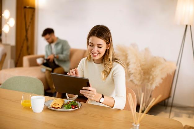 Mujer joven con tableta digital y desayunando en la cocina con un novio sentado