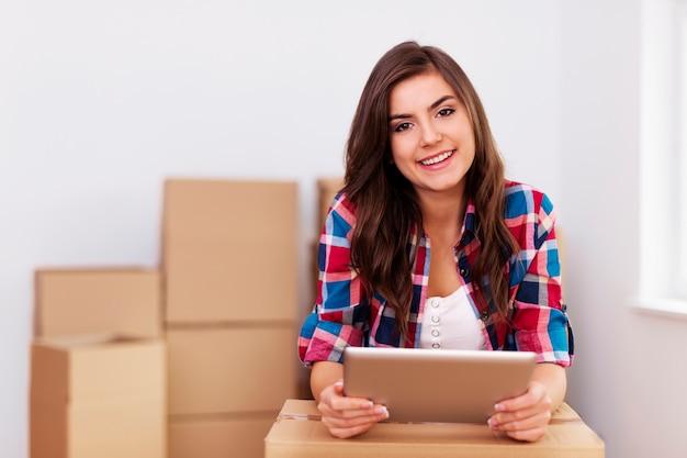 Mujer joven con tableta digital durante la mudanza en apartamento nuevo