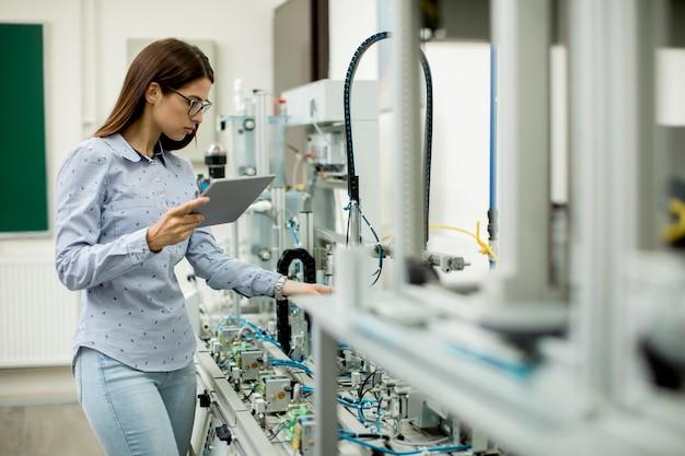 Mujer joven con tableta digital en el taller de electrónica